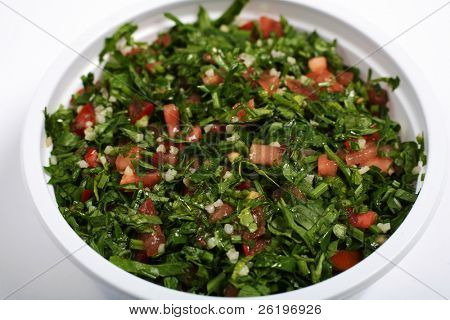"An Arab or Mediterranean tabouleh mezze of parsley, mint, onion, tomatoes, oil and spices, sprinkled with bulgar wheat, in a ""take-away"" pot."