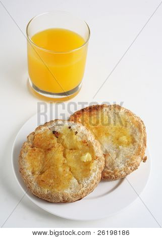 A plate with a split and toasted gluten free bun and a glass of orange juice, a healthy breakfast for someone with a gluten intolerance.