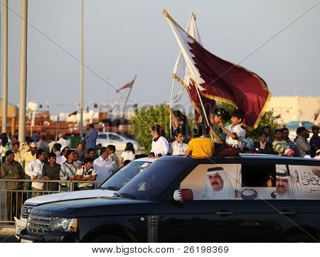 DOHA, QATAR - DECEMBER 18: Qatari families celebrate Qatar National Day with a cavalcade on the Corniche road in Doha on Dec 18, 2010. The Emir's photo is on the windows.