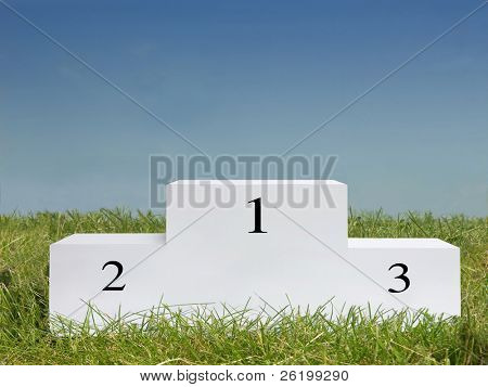 White podium on the grass against clear blue sky