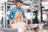 Affectionate Boyfriend Standing Near Table And Hugging Beautiful Girlfriend In Cafe poster