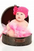 Beautiful 4 month old american baby girl sitting in travel case over white background.