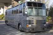 picture of groupies  - the bus for a rock band hides below a freeway overpass - JPG