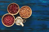 Assortment Of Kidney Beans In Wooden Dishes And White Kidney Beans In Linen Bag On Dark Blue Wooden  poster
