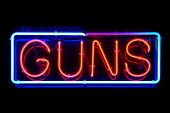 image of gun shop  - Guns neon sign isolated on black background - JPG