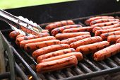stock photo of hot dog  - Rows of hot dogs on barbeque grill at park - JPG