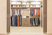 Modern Wooden Wardrobe With Clothes Hanging On Rail In Walk In Closet poster