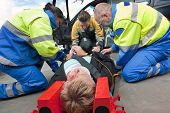 picture of neck brace  - Paramedics and a fireman strapping a wounded woman  with a neck brace on a stretcher - JPG