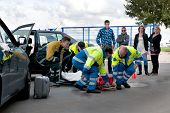 A team of emergency medical services at work, lifting an injured woman on a stretcher, to carry her