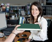 foto of librarian  - Young smiling female librarian handing a book to a customer - JPG