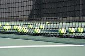 Постер, плакат: Net с многими теннисные мячи за Теннисный корт