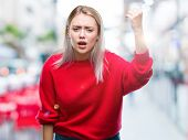 Young blonde woman wearing winter sweater over isolated background angry and mad raising fist frustr poster