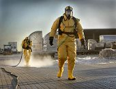 stock photo of environmental protection  - firemen in yellow protective clothing cleaning after little chemicals accident - JPG