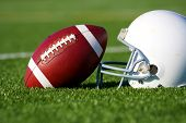 stock photo of football helmet  - American Football and Helmet on the Field with shallow depth of field - JPG