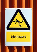 image of slip hazard  - Trip Hazard sign on an orange tin wall - JPG