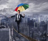 Equilibrist Businessman Walk On A Rope With Umbrella Over The City. Concept Of Overcome The Problems poster