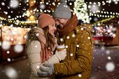 winter holidays, hot drinks and people concept - happy young couple with coffee at christmas market  poster