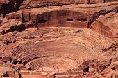 An aerial view of the Roman-era amphitheater carved into the pink sandstone at Petra, Jordan. The bu
