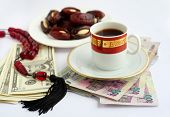 Coffee, dates stuffed with almonds and worry beads, on piles of Qatari Arab money and US dollars. Sw