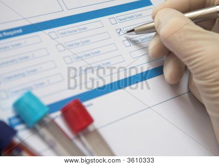 Doctor Completing A Blood Test Form