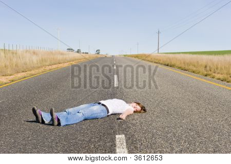 Deserted Country-Road With Girl Lying In The Middle.