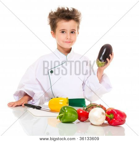 Little Boy Chef In Uniform With Knife Cooking Vegatables Holding Eggplant