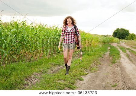 Young Redhead Woman With Guitar Passes Corn Field Outdoors In Summer