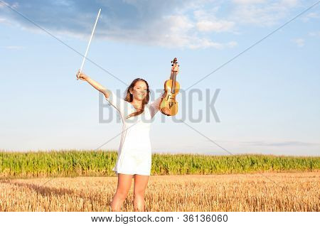 Young Woman Holding Violin And Bow Outdoors