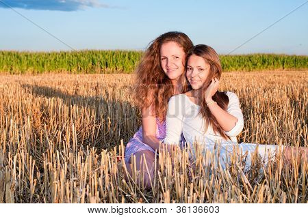 Two Girls Friends Lean Each Another On Summer Field