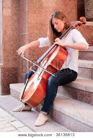 Woman Playing Cello On The Stairway Outdoors