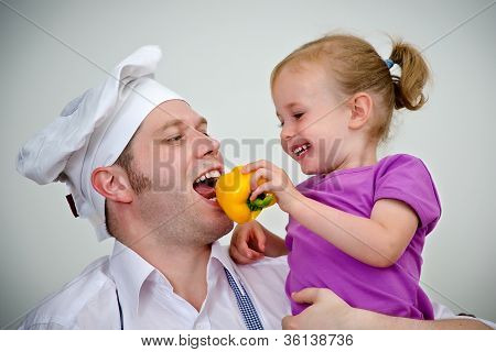Little Girl And Her Father Having Fun In The Kitchen