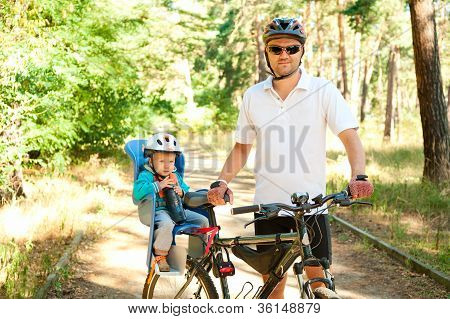 Father And Little Son On Bike With Child Seat