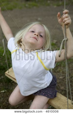 Litle Cute Girl Sitting On Swing. Summer Time