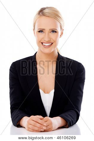 Adorable blond business woman sitting at desk  she looking at the camera  isolated on white