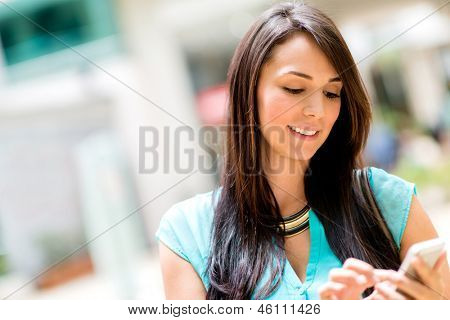 Woman sending a text message on her cell phone