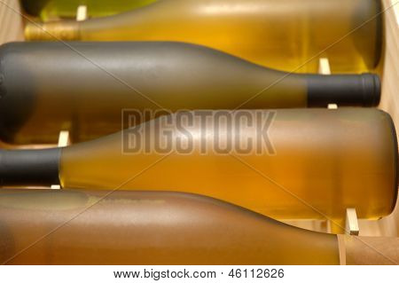 Closeup of a wooden crate of chardonnay wine bottles. Shallow depth of field, focus is on second bottle.