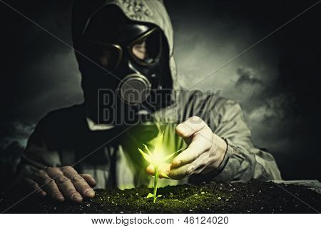 Young man in a protective suit touches to the sprout. post-nuclear future