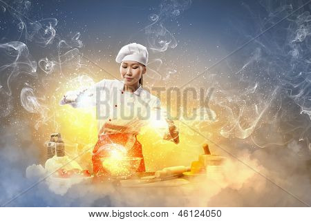 Asian female cooking with magic against color background