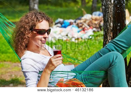 Young woman in dark sunglasses lies in hammock with glass of beverage, pile of garbage in background out of focus