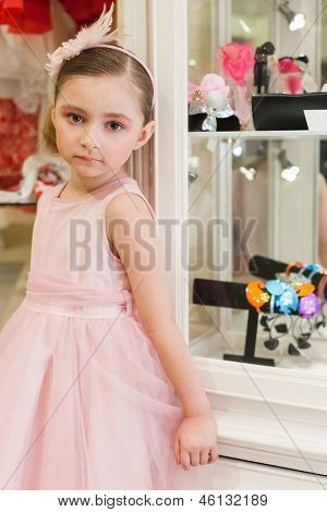 Beautiful girl in a pink dress in the shop of childrens bijouterie