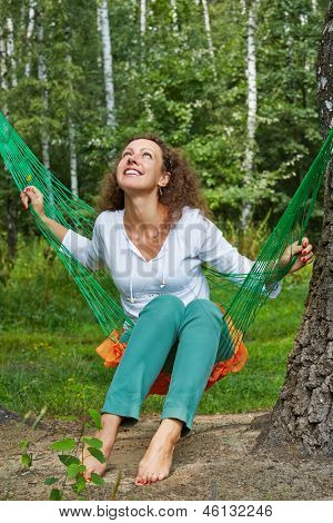 Young smiling woman with yellow flower in her hand sits in hammock and look at the sky