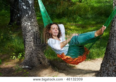 Young woman lies with dreamy view in hammock suspended between two thick birches