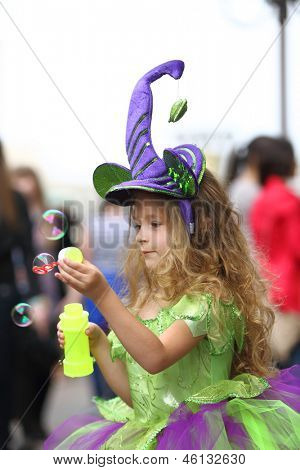 Little girl in fancy green dress catching soap bubbles on the holiday of spring and bubbles Dreamflash