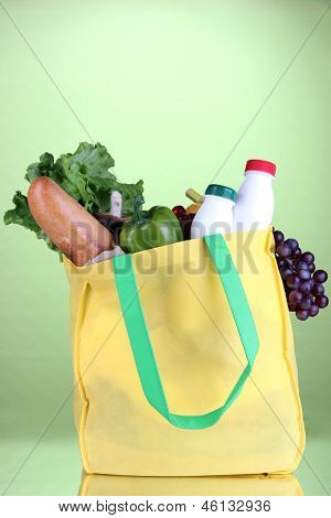 Eco bag with shopping on green background