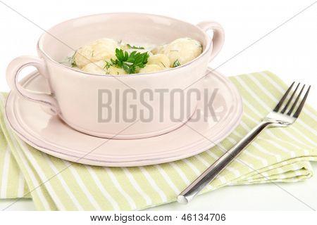 Concursos jovens batatas com creme de leite e ervas em pan isolado no branco