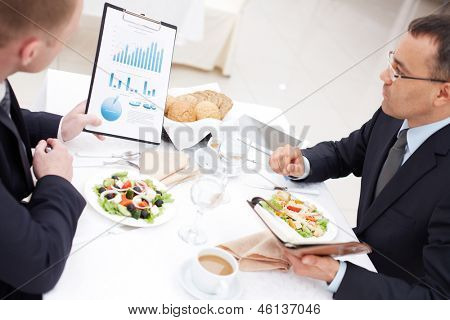 Confident businessmen discussing paper during business lunch