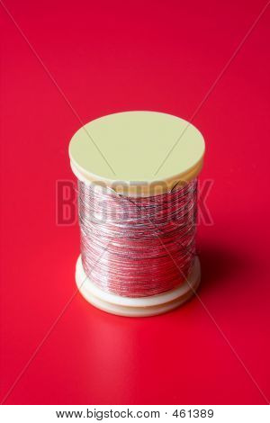 Bobbin Of Thread On A Red Background