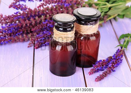 Medicine bottles and salvia flowers on purple wooden background