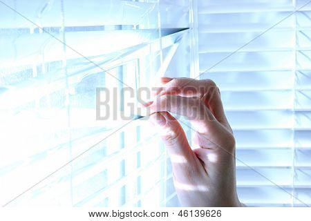 Someone looking out of window opening blinds