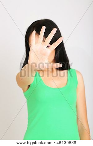 Girl showing stop sign on grey background